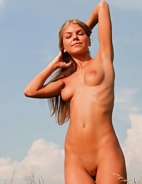 Inga Polina is a skinny long legged girl nude in the middle of a grassy field