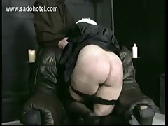 Naughty nun kneeling on a chair with her dress up and panties down is spanked on her well formed ass